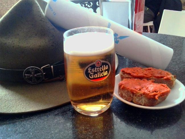 Birretta d'ordinanza e tapas celebrative, insieme alla Compostela (al sicuro nel suo tubetto di cartone).